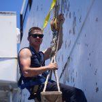 4/C Hallett scrapes paint aloft in a boatswain's chair